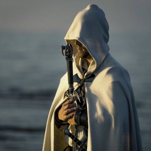 Portrait of assassin in white costume with the sword at the sea. Sunset time. Beautiful blue orange colors.